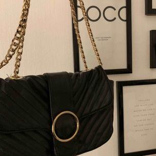 en suuuuperfin väska med guld-detaljer i fake skinn. ryms mycket i den, och kan bäras antingen över axeln i en kortare modell, eller som en crossover-bag!!!