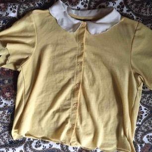 Jättesöt gul T-shirt med knappar i fram och vit krage! Bra skick och passar perfekt till något högmidjat. Vid frakt står köparen för fraktkostnaden 💌