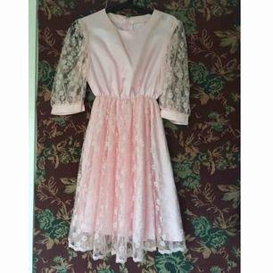 Rosa silkesklänning med spetskjol. Under spetsen går klänningen så det blir effekt av en underkjol, en ser alltså inte igenom. Sparsamt använd och i fint skick. Vid frakt står köparen för kostnaden 👼🏻