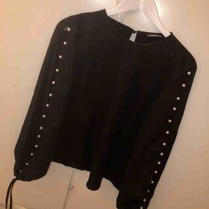 En jättefin svart blus med fina pärlor på ärmarna.   Aldrig använd!  Nypris - 149  Säljer den för 100kr + frakt  Storlek M (passar även S)