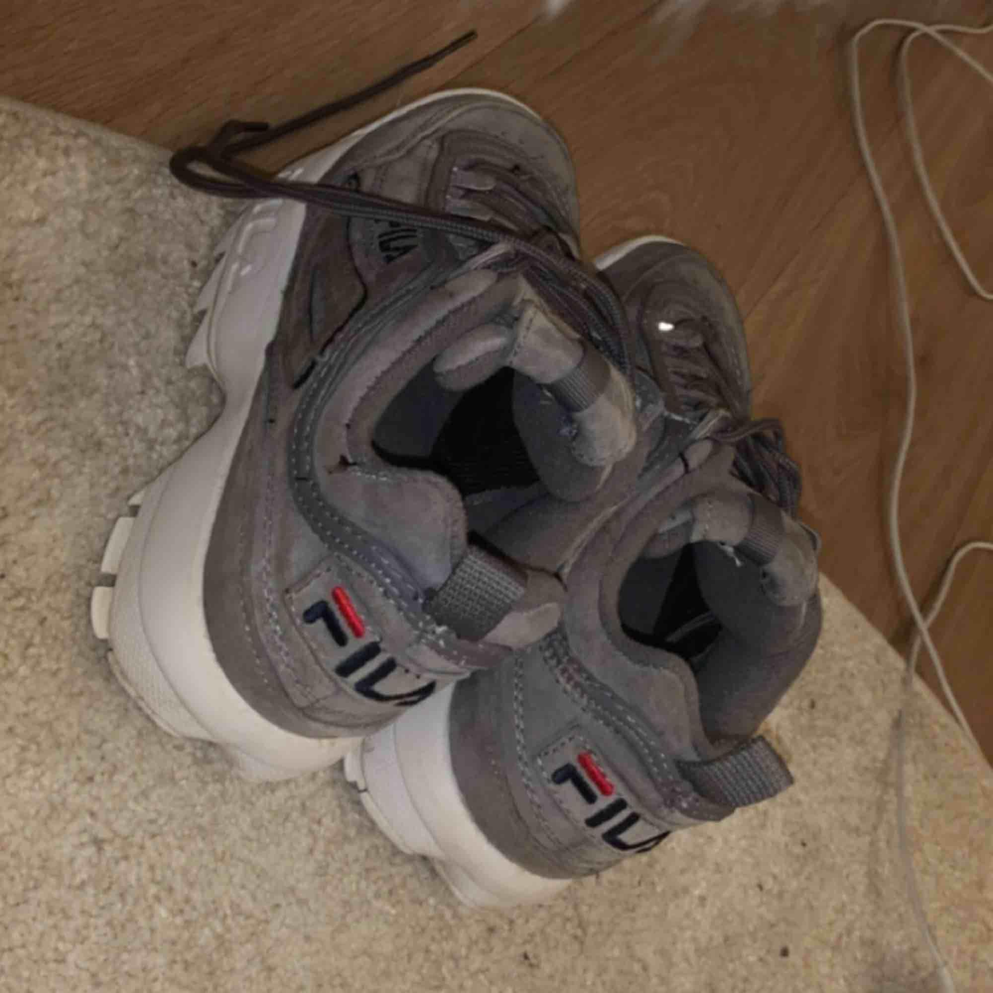Fila Disruptor skor i grå mocka. väldigt bra skick, använda endast ett par gånger. Skor.