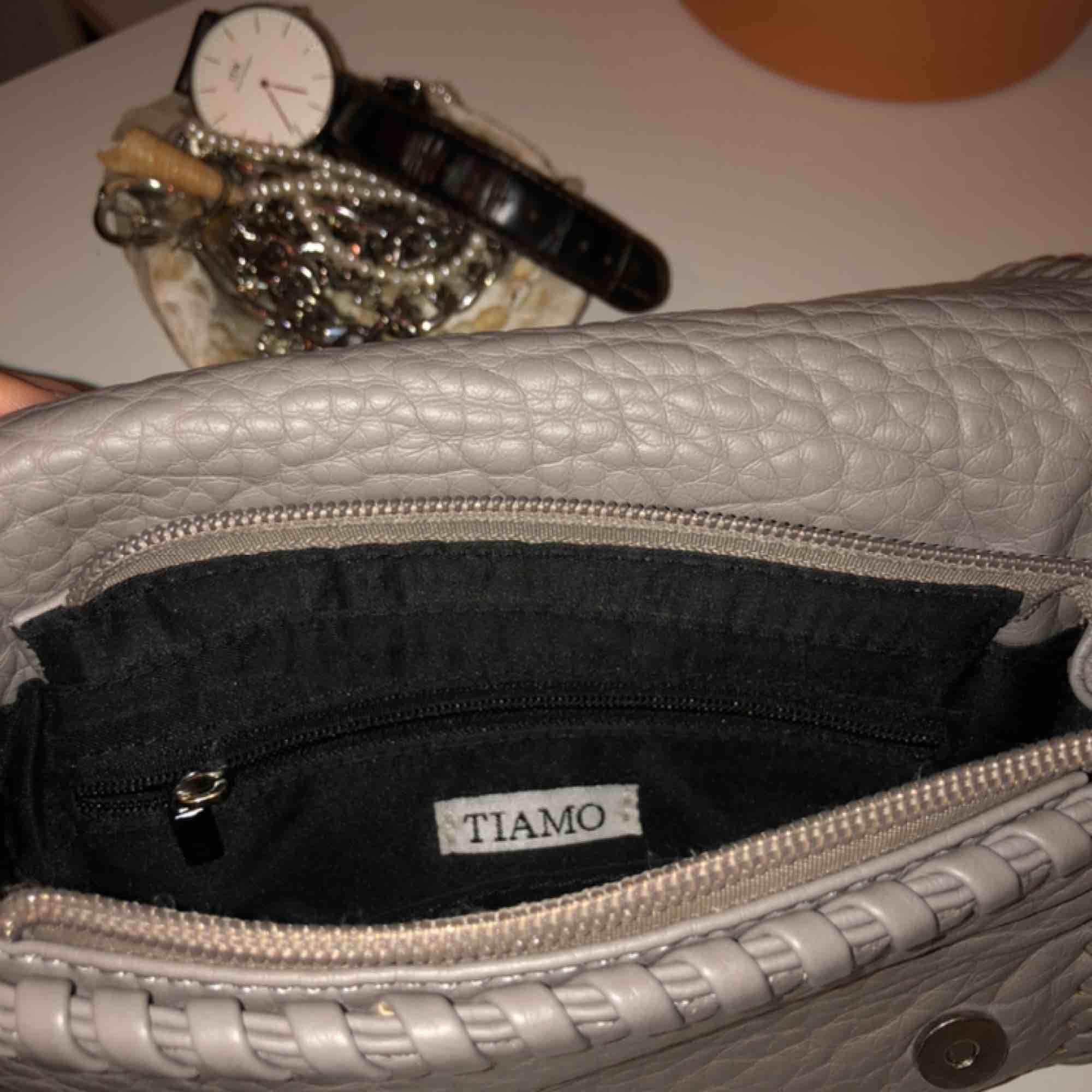 Väska från Tiamo i den minsta modellen med måtten 21x14x5. Är i jättebra skick, endast spännena på sidorna som blivit missfärgade, se bild 3. Nypris 450kr. Köpare står för frakt🦋. Väskor.