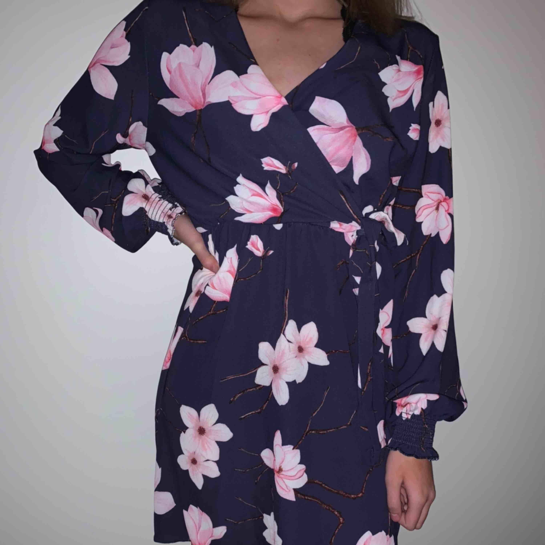 Blommig klänning. Aldrig använd, har prislappen kvar. Jätte jätte fin men har aldrig kommit till användning. Klänningar.