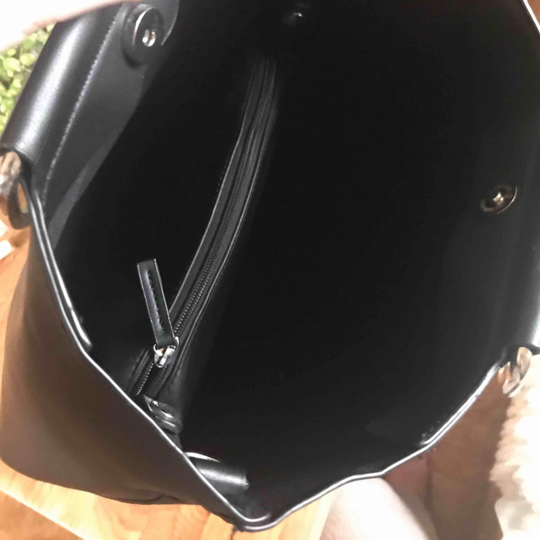 Mattsvart Carin Wester väska med silver handtag, långt band medföljer, helt oanvänd, 200kr+frakt. Väskor.