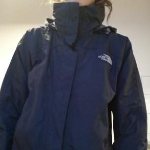 Svart vindjacka från The North Face i stl S med grått foder i kragen och på insidan av luvan. Luvan kan döljas genom att vika in den i kragen. Frakt 59 kr.