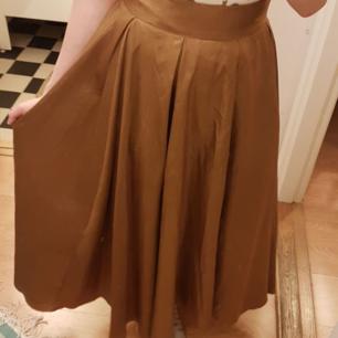 Guld/bronsaktig kjol, ankellång på mig som är 1.60. Kan mötas upp i Stockholm eller skicka mot frakt.