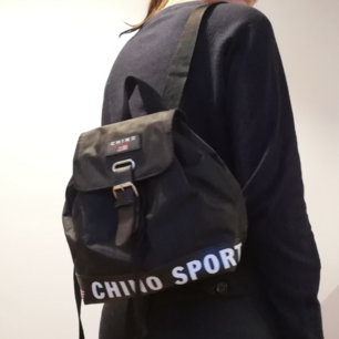 Svart sportig liten ryggsäck köpt secondhand. Lite Tommy Hilfiger inspirerad. I jättefint skick, enda att anmärka på är att spännet släppt lite, inget som påverkar funktionen och går nog att limma ihop. Säg till så skickar jag bild på det! Frakt 63 kr.