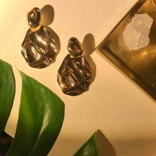 Fett snygga guldiga örhängen från NA-KD. Den stora delen av örhänget hänger bakom örsnibben. Knappt använda så örhängena är i nyskick! 95% zink 5% stål  Skickas mot fraktkostnad eller möts upp i gbg🥰