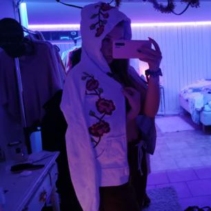 En vit hoodie med dragkedja, med brodyr på framsksan å över luvan