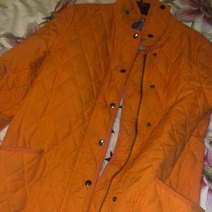 Snygg orange jacka, helt oanvänd och ny men råkade hamna på ett ljus därav ett litet brännmärke på baksidan som ni ser på bild tre. Frakt tillkommer