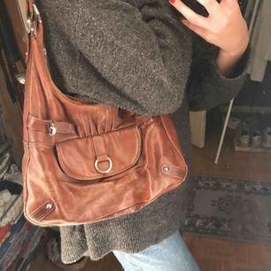 En superfin trendig brun väska!! Denna väska har jag mest använt som på bilden men man kan också koppla på ett band till! Det finns supermycket plats i den och passar både till jobb/skola och en middag!
