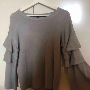 Grå tröja med utsvängda volangärmar. Skönt material, använd en gång. I nyskick :)  Frakt tillkommer priset