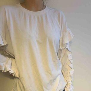 Skön långärmad tröja i vit. Har på ärmarna och ryggen en vit volang!