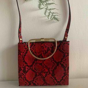 Supersnygg röd/svart väska med ormmönster. Bär den i det guldiga handtaget eller använd axelbandet. Två fack, passar perfekt till en dag på stan eller på fest.