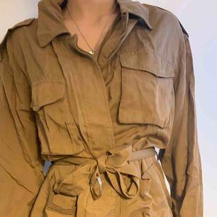 Ball jacka i brun. Snygg skjortkrage och bälte med silverdetalj. passar en vårdag, sommardag eller solig höstdag!