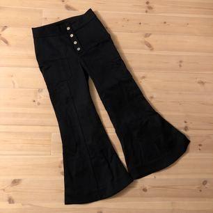 Mörkblå byxor med struktur från H&M Studio. Silverknappar, fickor utsvängda ben med slits på sidorna. Sparsamt använda.