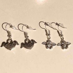 """Örhängen med texten """"Angel"""" på båda sidor i ett hjärta med vingar & örhängen med små silvriga änglar! Nickelfria. Båda för 100kr eller ett par för 59kr. (Fri frakt)"""
