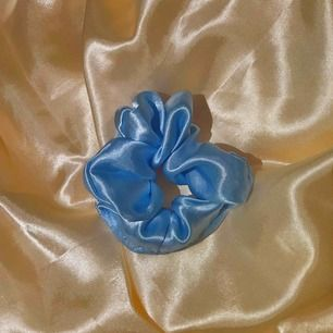 """Egensydd Scrunchie av ett silkigt material i en """"baby-blå"""" nyans. 25kr st  40kr för 2 st Skickar endast och då står köpare för den frakt som blir."""