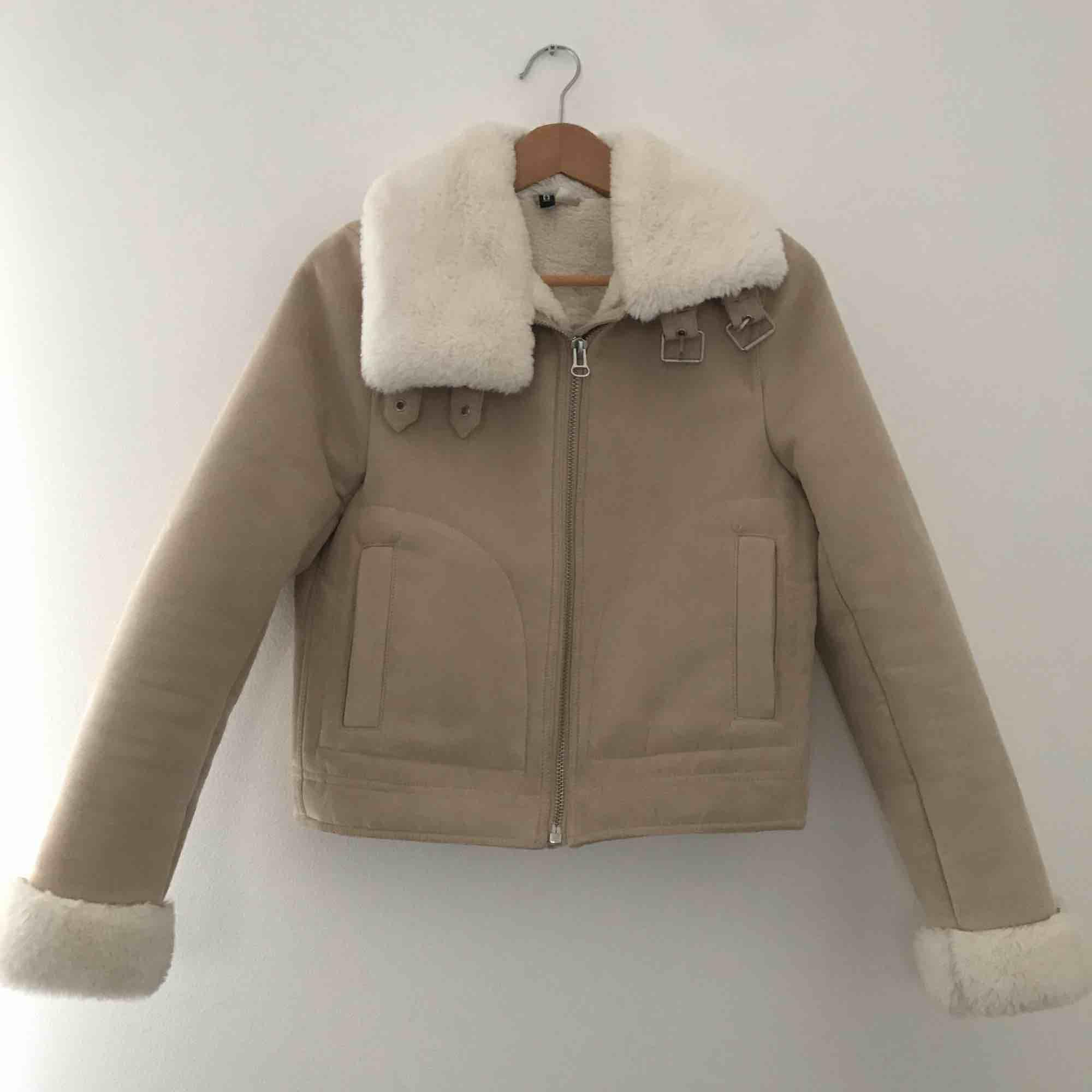 Snygg kort vinterjacka från H&M i beige mocka med vit fuskpäls i kragen och muddar på ärmarna. Fint skick!. Jackor.