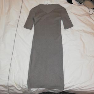 Grå klänning med ribbningar åt olika håll! Köparen står för frakt!