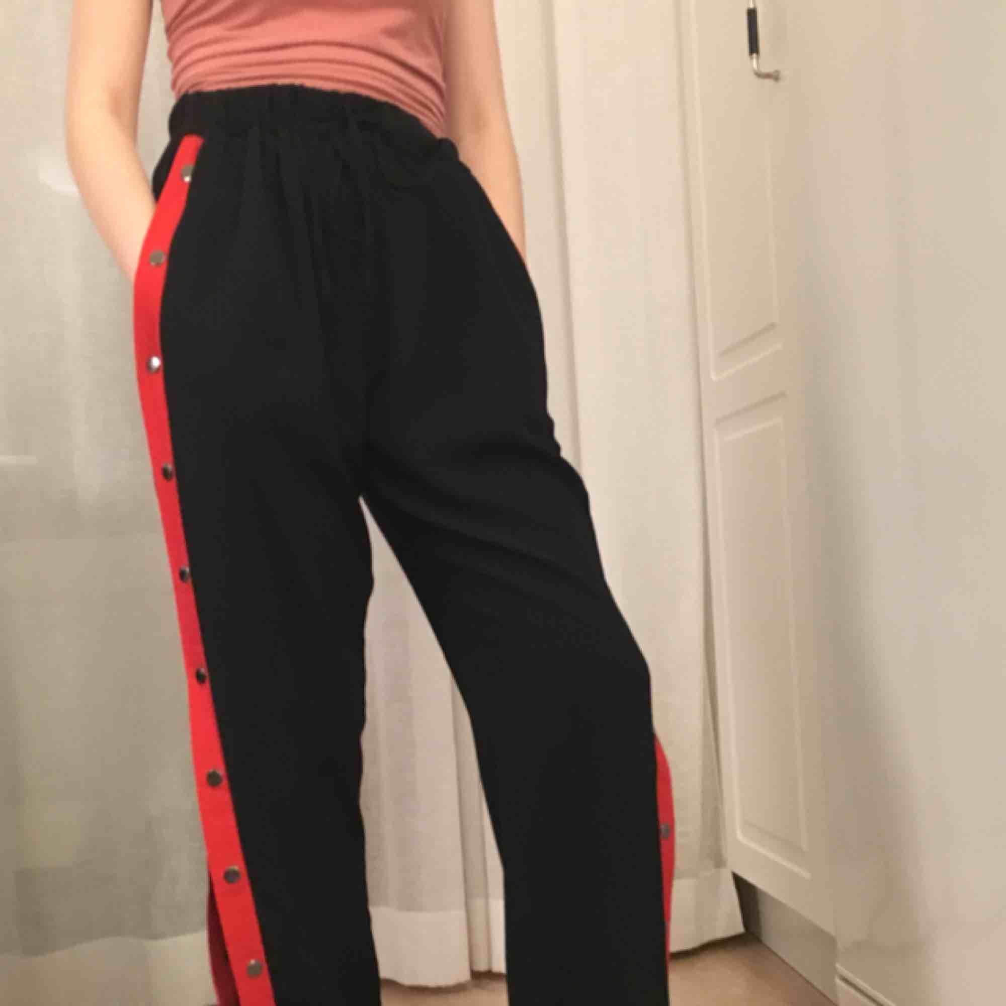Svarta popperpants med röd kant. I storlek S men skulle även passa M. Snygga, men inte riktigt min grej så att säga.. Jeans & Byxor.