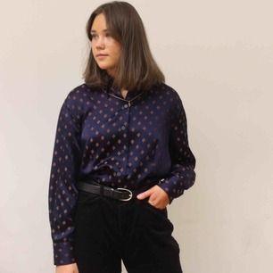 En blå skjorta med ett modernt mönster, materialet är i silke och funkar perfekt till vardag men även till fest🤩