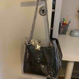 """Snygg transparent väska i plast med """"J'adore"""" tryckt på framsidan. Svart liten väska följer med som man kan ta bort.  Använd max 2 gånger.  Frakt 70kr tillkommer"""