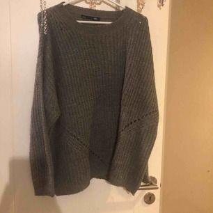 En grå stickad tröja, (sticks inte) den är lite större i storleken
