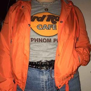 En neon-orange vindjacka från H&M's Divided-sektion. Helt oanvänd och i fint skick! Grått innertyg som värmer lite, bra att ha som ett lager under vinterjacka t.ex. Jackan sitter smickrande på alla kroppstyper!