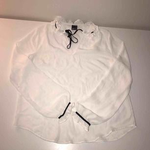Vit blus från Gina tricot med svarta detaljer. Priset är inklusive frakt