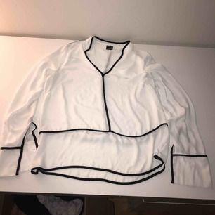 Vit skjortblus med svarta detaljer. Har inkluderat frakt i priset.