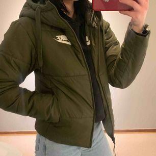 Varm vinter jacka, märke Nike. Knappt använd väldigt fint skick. Militärgrön färg och man kan även vänta ut och in på jackan och få fram ett stort nike märke på ryggen. Köpte den för ungefär 1000kr.