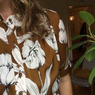 Otroligt fin bohemisk klänning ifrån Lindex, storlek m. Brun botten med vita blommor, knyte och resår i midja, ganska rymlig så den passar även L.  Fina detaljer