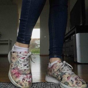 Fräcka skor som är sparsamt använda. Stl. 37 åt det mindre hållet. Tyget är ett blommigt mönster och en varmt färgad plastfilm över delar av skon är vattenavvisande. Kan mötas upp i Lund/Malmö eller frakta, köparen står för frakt