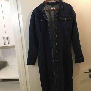 Lång jeansjacka. Kan användas som klänning och jacka. Sidfickor i sidan. Nyskick