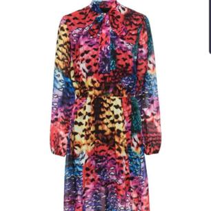 Vacker och färgglad knälång klänning/midi, 126 cm. Rosett i midjan. Använd 1 gång. ❣ Det vita bältet följer inte med. Yttermaterial: 100%polyester, Foder: 100% polyester