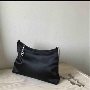 Så fin svart väska med dragkedja, har även ett innerfack (utan dragk). Bra skick,glansigt material. Kedja som handtag, den är lite längre men om man vill kan man knyta en knut så den blir kortare till axelremsväska eller byta handtag. Köparen betalar f
