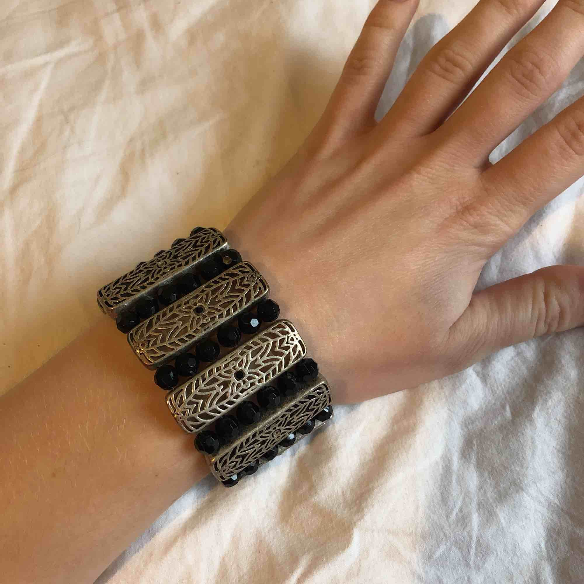 Silvrig metall med svarta slipade pärlor i plast. Totalt 18 cm långt med bra stretch för att få på och av. Tre av de små svarta pärlorna på silverdelarna saknas men det märks knappt.. Accessoarer.