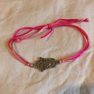 fint armband med hamsahanden med ett rosa reglerbart band