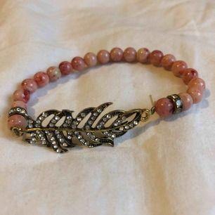 metallfjäder dekorerad med vita glittriga stenar, armband med rosa spräckliga pärlor. ca 16 cm omkrets med lite stretch. i princip oanvänt.