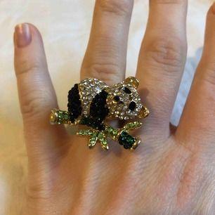 En pandaring med glittriga stenar/pärlor där själva ringen är guldfärgad men lite avskavd färg på undersidan. Annars fint skick.