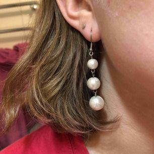 Örhängen med plastpärlor i tre olika storlekar. En vit glansig pärlfärg i grunden med ett vitt abstrakt mönster på.