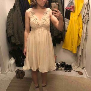 En beigefärgad klänning med lite tyll nertill på underkjolen och fina detaljer vid bröstet. Använd 1 gång så i mycket fint skick. Smock baktill i ryggen så passar nog en strl större också.