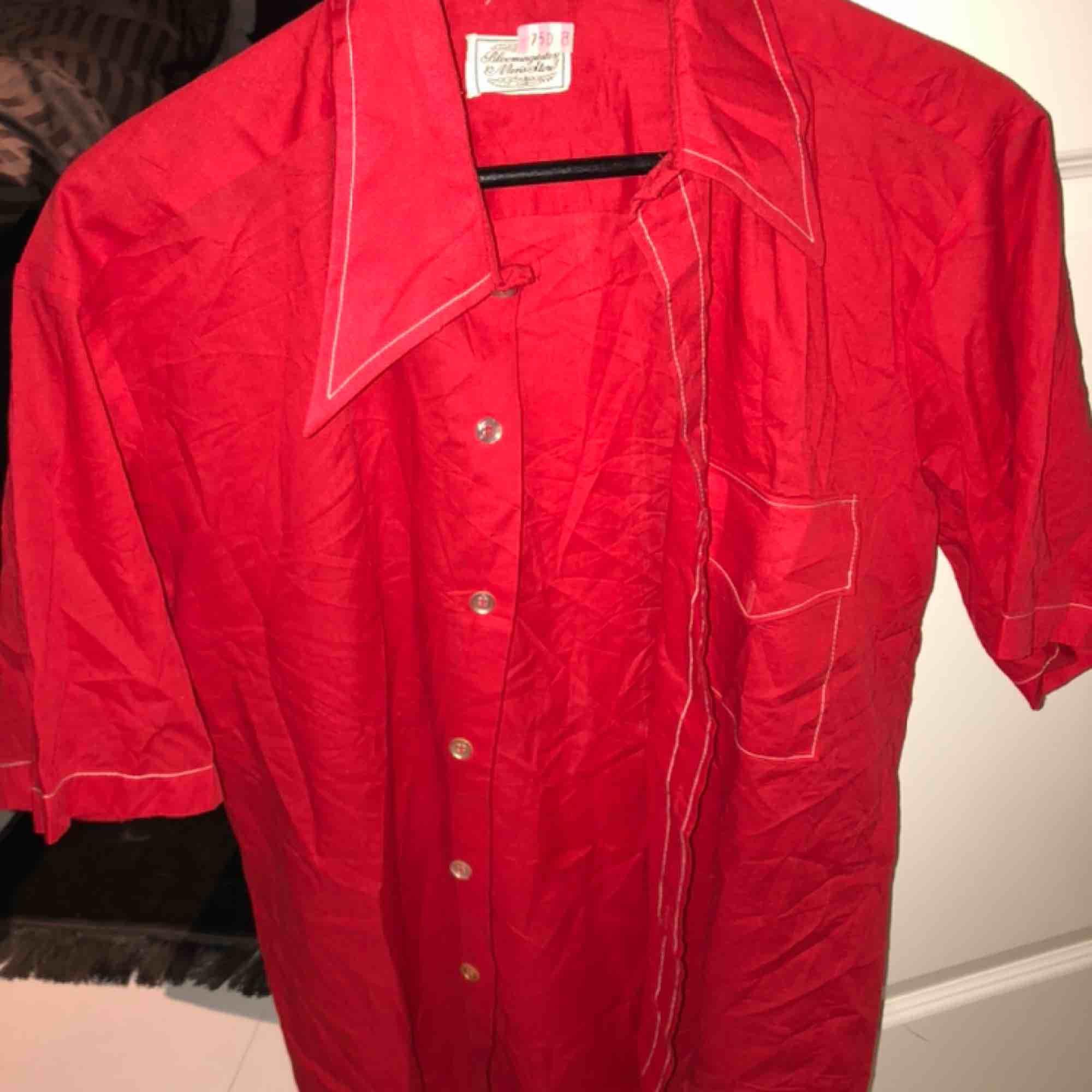 En oversized röd kortärmad skjorta från humana  Storleken är lite oklar men den passar alla beroende på hur man vill ha den. På mig som är 165 går de lite längre än ner till midjan   För övrigt använd typ 1 gång så den är i fint skick! ❤️🥰   . Skjortor.
