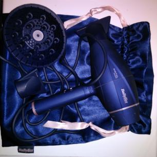 I fin påse från Babyliss 6500e med tillbehör. - Ny generations 2100 Watt EC digital motor ger fantastisk livslängd - Snygg blå design - Extremt snabb torkning av ditt hår med en luftström upp till 130 km/h - Automatiskt justerbart luftflöde beroende på vilket tillbehör du använder - Skonsamt och intensivt läge - Konstant temperatur på 70 grader gör ditt hår blankt och livfullt - Jonisk-teknik omtverkar statiskt hår och trassel - Tre tillbehör för proffsig styling av ditt hår. Ett munstycke för torkning, ett munstycke för att räta ut ditt hår och en diffusor ingår. - Cool Shot för fixering av frisyrer - Enkel hantering tack vare sin låga vikt på endast 621 gr - Bakre filtret är utrustad med en ljuddämpare som reducerar ljudet - 280 cm lång kabel