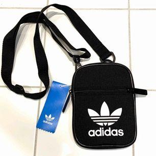 Ny liten, oanvänd väska från Adidas med tags kvar. Justerbart axelband, stängs med dragkedja. 90kr, köparen står för frakt, 40kr ✨
