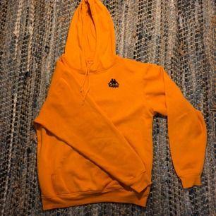 Kappa hoodie i fin orange färg. Den är i storlek L men skulle säga att den är som M. Fint skick.