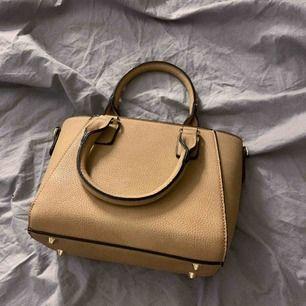Liten handväska i beige med guldiga detaljer, knappt använd och därför i gott skick. Säljer pga att den inte kommit till användning. 💞