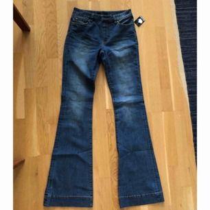 HELT NYA bootcut flare jeans oanvända med lapp kvar! Hög midja, fickor, skärphylsor. Midjemått 70cm, innerbenslängd 82cm. Fina 70-talsinspirerade. Nypris 399kr