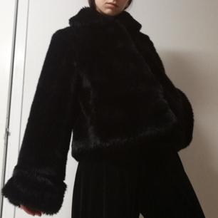 Stor svart fluffig faux fur från H&M Trend i stl S. Vida ärmar och lite utställd modell. Knäpps med hyskor. I bra skick. Frakt 63 kr.